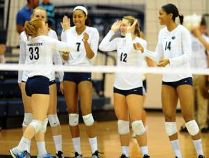 <p>Lacey Fuller (33) is greeted by Nia Grant (7), Micha Hancock (12), and Aiyana Whitney (14) during player introductions before the match against DePaul in Rec Hall on September 19, 2014. Penn State won in straight sets (25-8, 25-10, 25-13).</p>