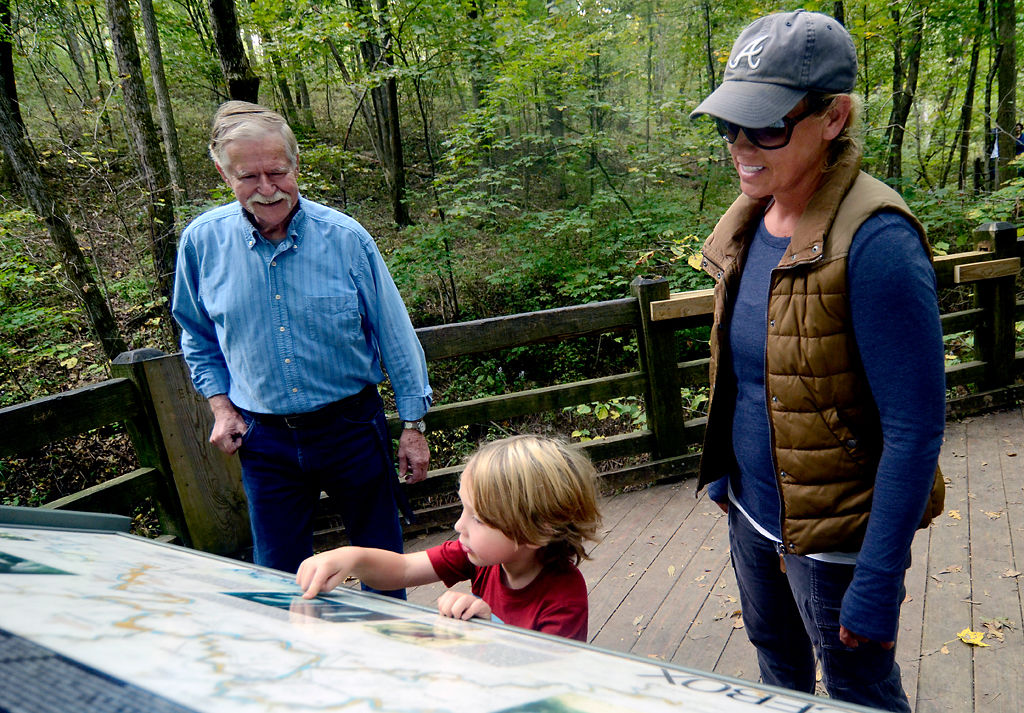 Earl Duncan, left, tells Erin Carr and her son about his adventures