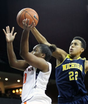 <p>Virginia guard Breyana Mason (12) has her shot tipped by Michigan forward Cyesha Goree (22) during the second half of an NCAA basketball game on Thursday in Charlottesville, Va. Photo / Ryan M. Kelly / The Daily Progress</p>