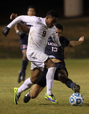 <p>Virginia forward Darius Madison (9) tries to get the ball past Connecticut defender Kareem Morad (13) during the second half of an NCAA soccer match on Friday in Charlottesville, Va. Photo / Ryan M. Kelly / The Daily Progress</p>
