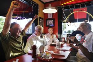 <p>Democratic vice presidential candidate Sen. Tim Kaine, D-Va., left, cheers while talking about sports over breakfast with friends at City Diner in Richmond Tuesday.</p>