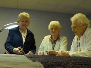 "<p>Billie Ann Spitler and Miriam ""Mimi"" Handley pin the front, batting and back of a quilt together on Tuesday, April 15 in Staunton.</p>"