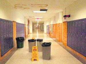 <p>Trash cans sit in the hallway, collecting water leaking through the ceiling at Waynesboro High</p>