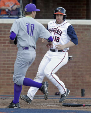 <p>Virginia catcher Nate Irving (18) crosses home plate next to James Madison pitcher Ben Garner (11) during the game against James Madison University Tuesday in Charlottesville, VA. Photo/The Daily Progress/Andrew Shurtleff</p>