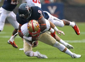 <p>Virginia strong safety Anthony Harris makes a diving tackle of VMI wide receiver Dane Forlines in the first half of the football game at Scott Stadium in Charlottesville, Va. Photo / Ryan M. Kelly / Daily Progress</p>