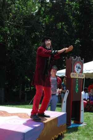 <p>Mark Cline, dressed as Willy Wonka, raises his hands to the sky, attempting to grow flowers.</p>