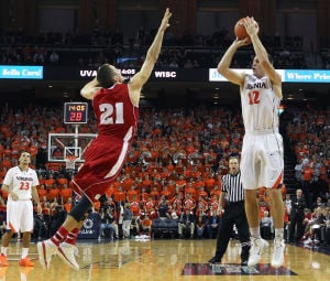 <p>Virginia guard Joe Harris (12) takes a shot over Wisconsin guard Josh Gasser (21) during the second half of an NCAA basketball game on Wednesday in Charlottesville, Va. Photo / Ryan M. Kelly / The Daily Progress</p>