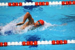 """<p><span style=""""color: #000000;""""><span style=""""font-family: 'Times New Roman', serif;""""><span style=""""font-size: medium;"""">Justin Merritt, 17, swims in the freestyle event</span></span></span></p>"""