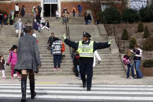 <p>Crossing guard Ruth Hill directs traffic and pedestrians on Monticello Avenue in front of Clark Elementary School in Charlottesville. Hill was named one of Virginia's Safe Routes to Schools most outstanding crossing guards.</p>