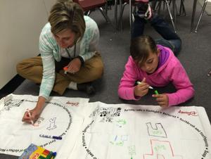 """<p align=""""right"""">PAT FITZGERALD/GREENE COUNTY RECORD</p><p><strong>Nathanael Greene Elementary School Principal Anne-Marie Eberhardt and fifth-grader Kara Baker-Jones use felt markers to draw on the outside of their pillowcases to keep items in in case of an emergency. The Virginia Mountain Region of the American Red Cross last week showed NGES students how they can help their own families by using """"Pillowcase Project.""""</strong></p>"""