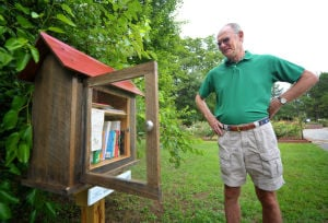 <p>Randy Bryson looks over the Little Free Library house that he built next to the rose garden at the Dothan Area Botanical Gardens.</p>