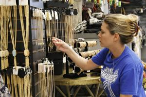 <p>Kendra Johnson/Gazette Lori Hodge looks at necklaces in the clothing store French Lily. She said that the store looks cute and everything they are selling looks good and that she hopes the store does well.</p>