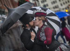 <p>Matthew and Kei Hoffmann of Austin share a kiss under their umbrellas at Dickens on The Strand in Galveston, Texas Saturday, Dec. 3, 2016. Visitors to the annual festival braved inclement weather. Organizers waived admission fees for the weekend and announced that the festival would be held again Friday, Dec. 9 and Saturday, Dec. 10.</p>