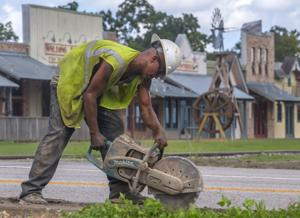 <p>Construction worker Rudy Soto cuts asphalt for new sewer lines on Main Street across from Walding Station in downtown League City on Wednesday.</p>
