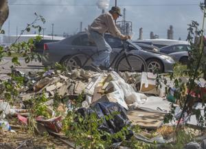 <p>Garbage is strewn by the side of an unpaved alley near Texas Avenue in Texas City Thursday, July 14, 2016.</p>