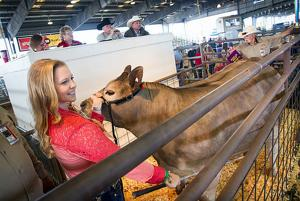 <p>Breanna Gates of Santa Fe smiles as the bids come in for her Grand Champion Steer Beavis at the Galveston County Fair and Rodeo Youth Livestock Auction in Hitchcock Wednesday, April 15, 2015. </p>