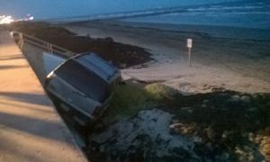 SUV goes over seawall