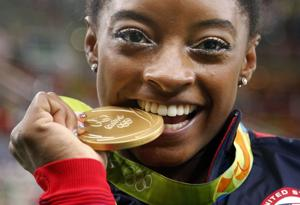 <p>United States' Simone Biles bites her gold medal for the artistic gymnastics women's individual all-around final at the 2016 Summer Olympics in Rio de Janeiro, Brazil. Briles was selected as the AP Female Athlete of the Year, on Monday.</p>