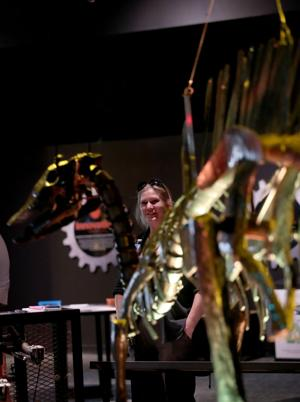 """<p>Kelly Teichmiller, an exhibit specialist in the Education Department at Moody Gardens, talks about the interactive, life-size dinosaur sculptures created by artist John Payne on Thursday. Paynes' recycled metal dinosaurs are part of Moody Garden's newest exhibit """"Dinosaurs in Motion.""""</p>"""