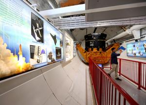 <p>Informative panels and artifacts from the space shuttle program line either side of the walkway that extends into the payload bay of the shuttle replica Independence at Space Center Houston's new Independence Plaza. The space center's newest exhibit, which opens Saturday, showcases the training shuttle and the shuttle carrier aircraft, NASA 905.</p>