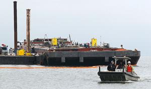 Crews work to repair disabled barge