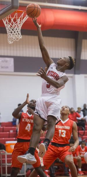 <p>Hitchcock's Alfred Locke lays the ball up against Stafford's Christopher Brantley (4) and DeQoriyahn Hawkins (13) during the second quarter at Hitchcock High School on Dec. 16, 2016.</p>