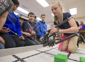 <p>Barber Middle School fifth grader Kaydin Gravitt places a robot that she and her classmates built onto a board in her classroom at the school in Dickinson on Thursday, Jan. 12, 2017.</p>