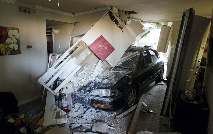 Car crashes through apartment