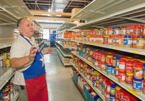 <p>Noe Sanchez, manager of the Interfaith Caring Ministries' food pantry, talks about how things are shelved.</p>