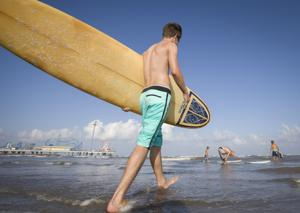 <p>Michael Gienger, pastor at Central United Methodist Church in Galveston, walks into the water with his longboard during a meeting of the Couch Surfers Bible study group in Galveston Tuesday, July 12, 2016.</p>