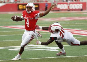 <p>Houston Cougars D'Eriq King gets away from Lamar Cardinals defensive back Rodney Randle on a four yard rush during the second quarter on Saturday afternoon September 10, 2016 at TDECU Stadium in Houston. The Cougars defeated the Cardinals 42-0.</p>