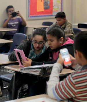<p>Jennifer Renovato and Paloma Ayala share a tablet as they review for their upcoming social studies test in Britta Carter's class at Shamarion Barber Middle School in Dickinson. For the review, the students were using Kahoot, a website that allows teachers to create multiple-choice tests and turn it into a Web-based game.</p>