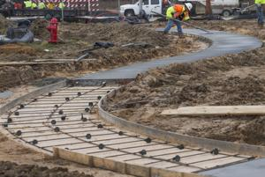<p>Construction workers install a sidewalk on Tuesday in the new Lago Mar subdivision in Texas City.</p>