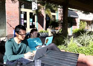<p>Ramon Mendoza and his wife, Yana, work on their laptops outside Mod Coffehouse in Galveston. While customers connect on social media, they also are choosing to spend more time with people in their community.</p>