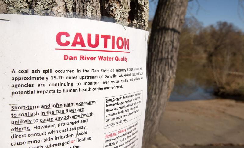 This sign, stapled to a tree at Abreu-Grogan Park in Danville, Va., advises citizens of a coal ash spill in the Dan River (background) that occurred about 20 miles upstream in February 2014. Photographed at the park on Wednesday, April 2, 2014.