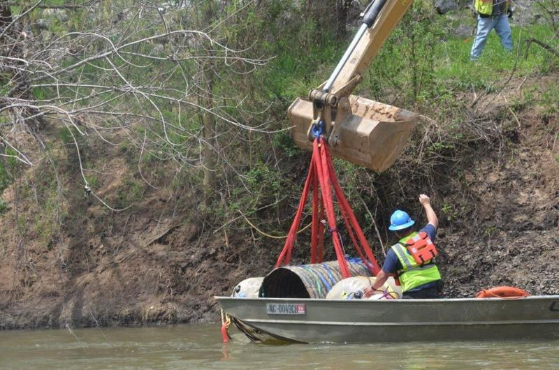 Workers lift a section of damaged pipe from the Dan River near the Duke Energy coal ash pond in Eden, in April. - Duke Energy Photo