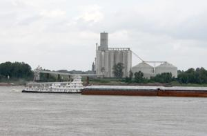 <p>A TUG (top photo) heading north pushes several barges of grain by the Bunge grain elevator on the Mississippi at Vidalia. (Photo by Rhett Powell)</p>