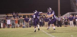 <p>Jakarie Nichols (2) takes a handoff from Ridge Heisler (13). Nichols had a 72-yard touchdown and intercepted two passes in Manghams' 40-20 Homecoming win over St. Frederick. </p>