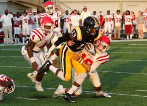 <p>Neville senior Quintin Guice (13) looks for daylight as Ruston's Seth White (19) makes the tackle.</p>