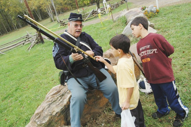 Brothers learn about civil war era rifle.