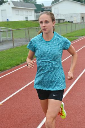 <p>John F. Brothers | Herald-Standard</p><p>Marathoner Clara Santucci of Dilliner warms up with a run around the track at Waynesburg Central High School.</p>