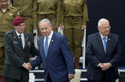 <p>Prime minister Benjamin Netanyahu, center, shakes hands with Deputy IDF Chief of Staff Yair Golan at a ceremony for outstanding soldiers as part of Israel's 68th Independence Day celebrations, at the President's residence in Jerusalem on May 12.</p>