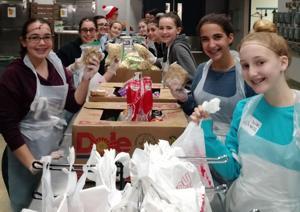 <p>Teens prepare food bags at St. Vincent de Paul during the Jewish Community Foundation's B'nai Tzedek Youth Philanthropy Tikkun Olam Tour on Feb. 5.</p>