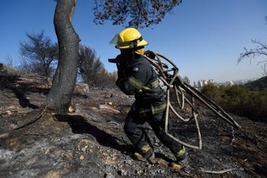 <p></p><p>An Israeli firefighter trekking through a forest burned by a massive forest in Haifa, Israel, Nov. 25, 2016. (Gili Yaari /Flash90)</p><p></p>