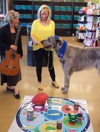<p>Leesa Weisz and her dog Maccabee attend the pet Passover seder led by Nurit Avigdor, left, at Choice Pet Market in Scottsdale.</p>