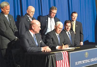 <p>Indiana Gov. Mike Pence ceremonially signs legislation requiring the state to divest from any business that engages in action to boycott, divest or sanction Israel on May 27. Looking on is Israel's ambassador to the United States, Ron Dermer, seated right.  </p><p>Screenshot from Twitter</p>