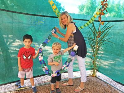 <p>Danny Bien-Willner and Matthew Garber hang decorations in the sukkah with teacher Ronni Farese at Temple Kol Ami Early Childhood Center.  </p><p>Photo courtesy of Debbie Glassman</p>