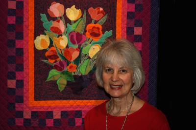 <p>Firber artist Sheila Groman stands before a quilt depicting posies.</p>