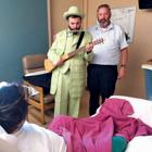 <p>Rabbi Eli Adler, left, and Yechezkel Friedman visit a patient at a local hospital on Purim, through Ezras Cholim of Phoenix, a nonprofit run by Friedman and Elchonon Gross that helps serve hospitalized patients and their families. </p><p><span><em></em></span></p>