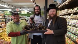 <p>Alexander Rapaport, co-founder of the Masbia Soup Kitchen, right, checks out organic horseradish with Yisroel Bass, director of the Yiddish Farm, center, and an employee of Organic Circle, an all-kosher organic supermarket in Brooklyn.</p>